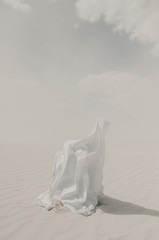 White on white concept with a white flowing fabric draped over a human sitting on sand