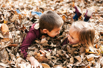 Autumn: Kids Playing In Big Leaf Pile