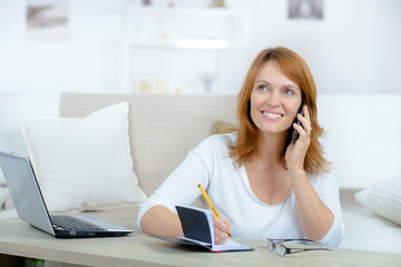 smiling woman talking on the phone working at laptop