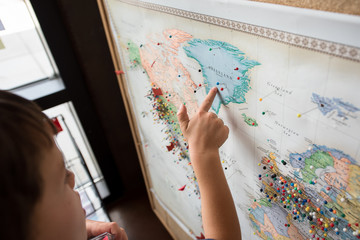 A boy points on a map where pins point out where people have visited from