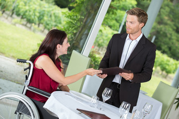 smiling woman in a wheelchair in a restaurant