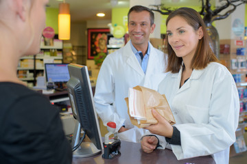 Pharmacist passing paper bag to customer