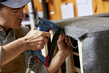 Male Worker Using Upholstery Gun On Armchair At Sofa Workshop