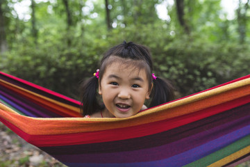 lovely little asian girl sitting in the hammock outdoor in the summer park