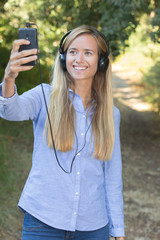 young university student taking selfie while listening music