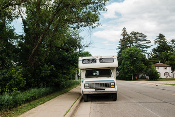 Vintage camper parked on a street in a small town.