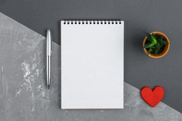 Open notebook, pen, heart and green flower on a gray background