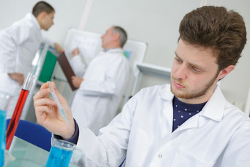young man lab worker holding up test tubes