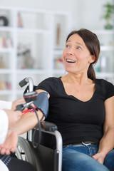 disabled woman having blood pressure measured