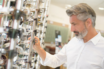 middle age man choosing glasses from shelf in optician shop