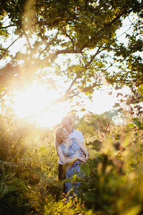 Dreamy portrait of young family with pregnant woman standing in sunset light