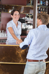 happy barmaid talking to customer