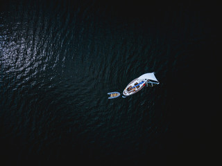 Aerial view of white yacht with little boat
