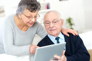 old couple looking camera with tablet pc in their hands
