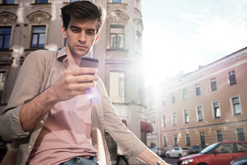 Handsome city dweller with smartphone