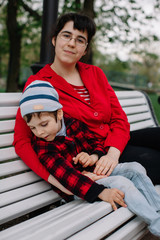 Older sister sitting on the bench with her brother with infant cerebral paralysis