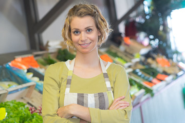 portrait of smiling woman in apron selling veggies