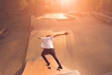 Male skateboarder doing midair tricks on ramp outdoor during sunset