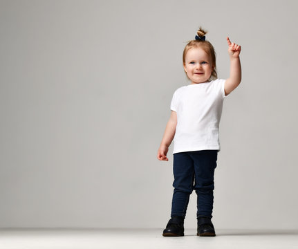 Toddler child baby girl kid standing in white free text space t-shirt pointing finger up
