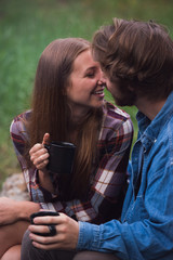 Couple warms up with a hot beverage near a campfire on a summer