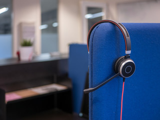 Computer or telephone headset hangs in an office or call center.