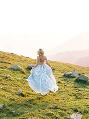 Woman in long dress running in mountains