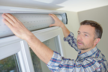 man installing blinds