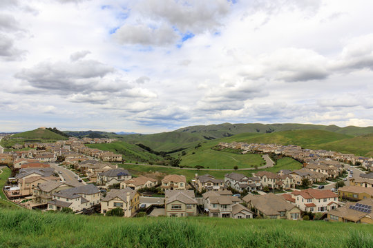 Residential Homes in Dublin Hills with approaching storm clouds in the winter. Dublin Hills Regional Park, Alameda County, California, USA.