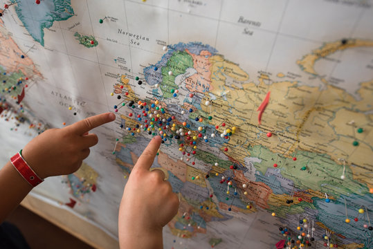 Children pointing at map with pins