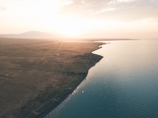 aerial shot of kazakh coastline from alakol lake at sunset