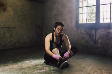Strong brunette woman resting after boxing workout.