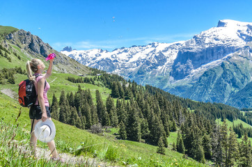 The girl watered herself with water from a bottle on the background of the Alpine landscape