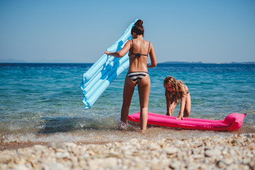 Mother and daughter entering water with inflatable beds