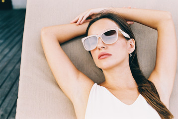 Overhead Closeup of Beautiful Brunette With Pink Sunglasses Relaxing on Sunbed