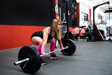 Athlete woman lifting barbell at gym