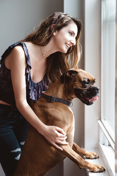 A young woman and her dog at home