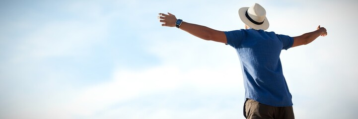 Composite image of low angle of a man raising arms up