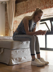 Woman sitting on ottoman with phone