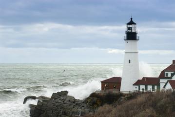 Waves Crash Against Maine Lighthouse as Sun Breaks Through