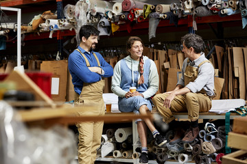 Happy Workers Discussing At Warehouse In Sofa Workshop