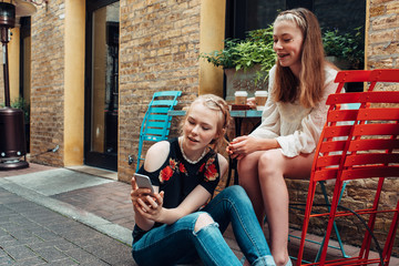 Two young girls checking a smartphone by a cafe table outdoors