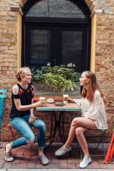 Two teen girls hanging out at cafe table outside