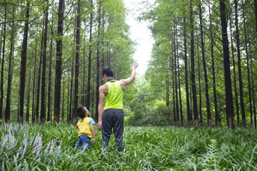 little asian boy in the woods on his father's shouder