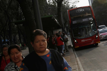 Commuters wait to board one of dozens of British double-decker buses, which is part of a one billion peso deal with Britain to help the sprawling capital tackle traffic and pollution in Mexico City, Mexico