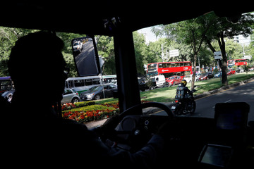 A driver steers one of dozens of British double-decker buses, which is part of a one billion peso deal with Britain to help the sprawling capital tackle traffic and pollution in Mexico City, Mexico