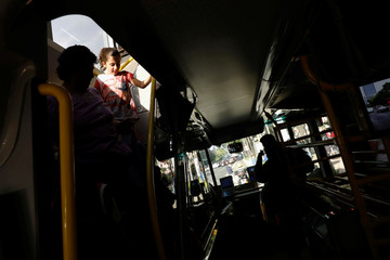 Commuters ride in one of dozens of British double-decker buses, which is part of a one billion peso deal with Britain to help the sprawling capital tackle traffic and pollution in Mexico City, Mexico
