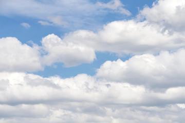 Cumulus and Cirrostratus clouds against a blue sky.
