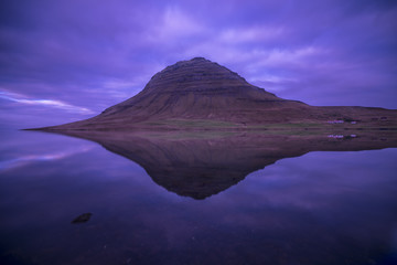 Long Exposure photography of kirkjufell Mountain with a lake in foreground and purple cloudy sky