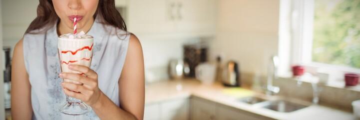 Composite image of young girl drinking milkshake