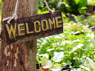 welcome sign hanging in the garden with space background